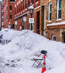 Folding chair and orange cone being used as a parking space saver on Endicott Street during the February storms.